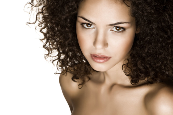 Image of a curly brazilian model wearing soft red lipstick and red blush.