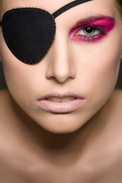 Beauty photography of makeup on a girl, in colors red or magenta, wearing an eye patch.